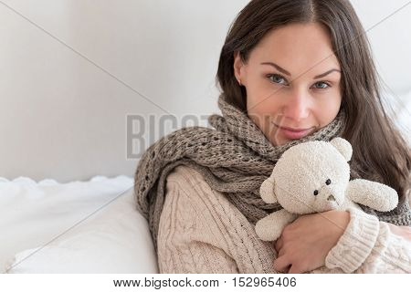 Favourite toy. Attractive cute happy woman hugging a teddy bear and smiling while looking at you