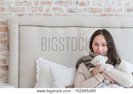Cozy and warm. Attractive delighted young woman wearing a knitted scarf and hugging a stuffed toy while resting in bed