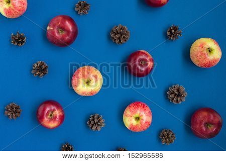 Fresh apples and pine cones pattern, top view