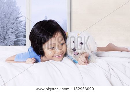 Portrait of a happy little girl hugging canine while lying in the bed with winter background on the window