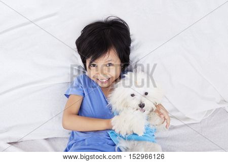 Unique perspective of a little girl hugging her puppy while lying in the bedroom