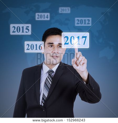 Young Asian businessman pressing numbers 2017 on the virtual button with world map background