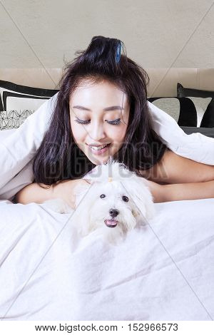 mage of beautiful woman holding maltese dog while lying under a blanket in the bedroom