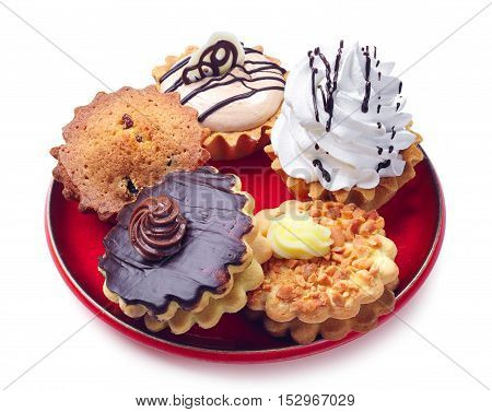 Different cupcakes in a plate on white