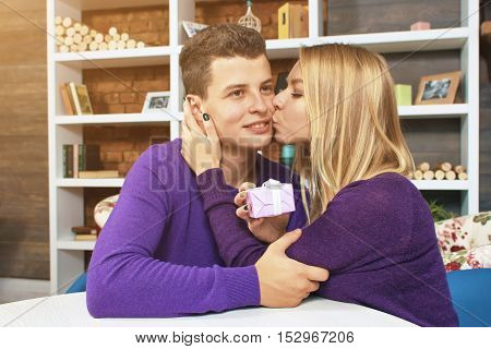Young girl kisses her boyfriend for the gift. The young man make gift and receives kiss