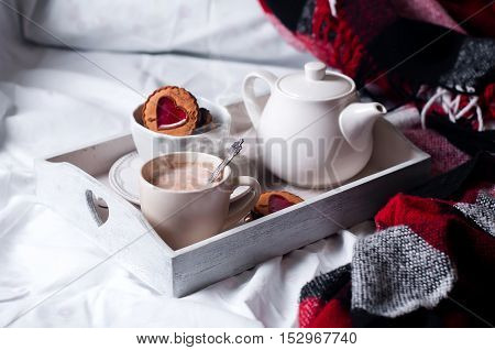 breakfast with coffee and cookies in bed with gray blanket.