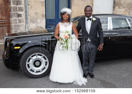 Portrait Of Bride And Groom In Front Of Luxury Car