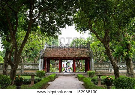 Hanoi Vietnam - September 20 2016: Entrance through green garden of temple or literature or first university in Hanoi Vietnam called Van Mieu - Quoc Tu Giam.