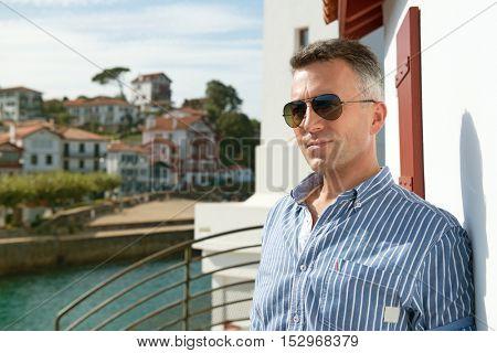 Handsome man. Outdoor male portrait. Middle-aged man resting at seafront, summer outdoor portrait, image toned. Saint Jean de Luz, France.