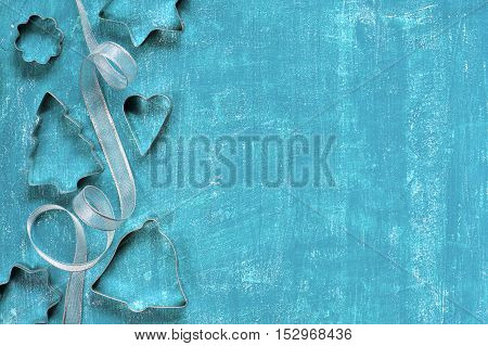 Painted blue aged background with metal molds and ribbon