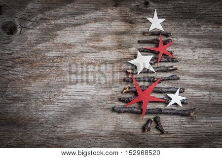 Branches With White And Red Stars In A Shape Of Christmas Tree On Rustic Wooden Background And Space