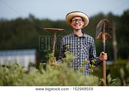 Young male farmer holding shovel and rake smiling in the garden