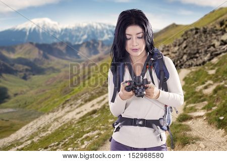 Portrait of woman looking pictures from a digital camera while standing on a mountain ridge