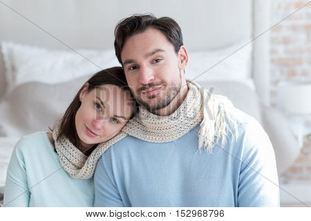 Male shoulder. Peaceful delighted brunette woman resting her head on the shoulder of her boyfriend and smiling while sitting side by side