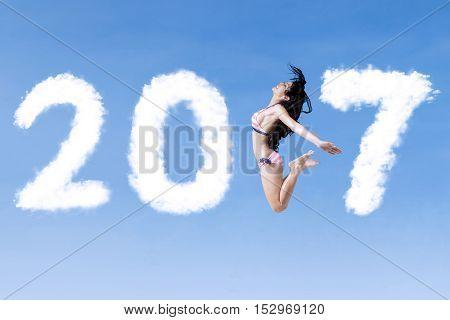 Joyful woman wearing bikini and jumping on the blue sky with number 2017
