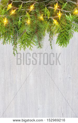 White wooden background with evergreen branches and garland