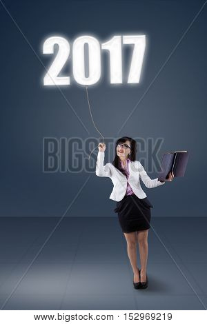 Portrait of a young Asian businesswoman holding a book and pulling numbers 2017