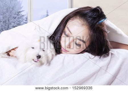 Image of young woman lying on the bed with her dog while sleeping under a blanket in winter season