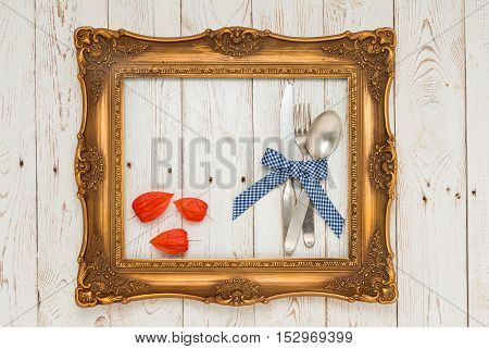 Cutlery In Picture Frame On Wooden Table