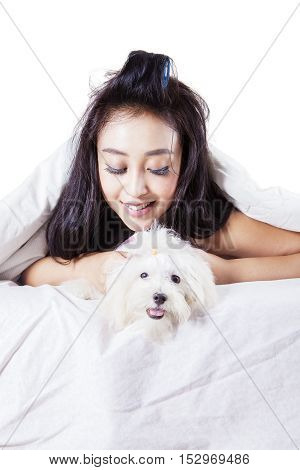 Happy woman lying on the bed with her maltese dog under blanket isolated white background