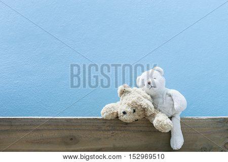 teddy bear on old wood blue wall background