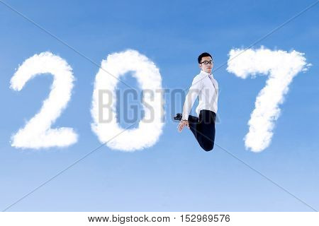 Photo of a young businessman jumping on the blue sky with clouds shaped number 2017