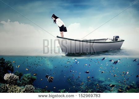 Picture of a young businesswoman standing on the boat while looking down at the sea