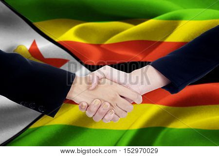 Close up of the Zimbabwe flag with two hands of business people handshake after closing deals a meeting