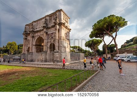 Rome Italy - September 12 2016: Tourists visiting The Arch of Constantine (Arco di Costantino) a triumphal arch in Rome situated between the Colosseum and the Palatine Hill in Rome.