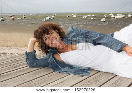 Woman Laying Down On Wooden Deck During A Summer Vacation.