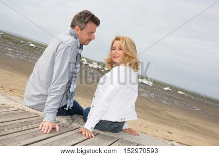 Smiling Couple Sitting On Wooden Jetty And Looking At Camera