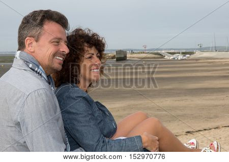 Middle Aged Couple Sitting On The Wooden Jetty