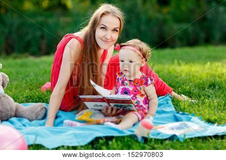 Girl with smiling mother with book sitting on plaid in park