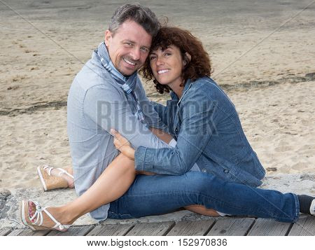 Smiling Couple Sitting On The Wooden Jetty