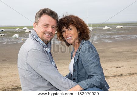 Happy Middle Aged Couple Sitting On The Wooden Jetty