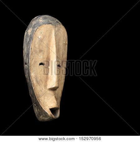 african culture carved mask on a black background