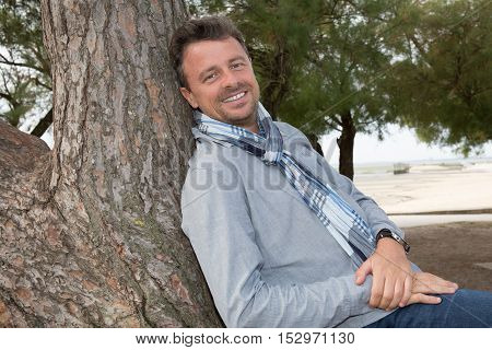 Smiling Middle Aged Man Relaxing In Countryside Leaning Against Tree