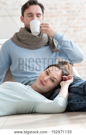 Spending time together. Attractive delighted woman lying on her boyfriend and smiling while enjoying their time together