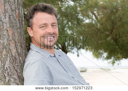 Cheerful Man Relaxing In Countryside Leaning Against Tree