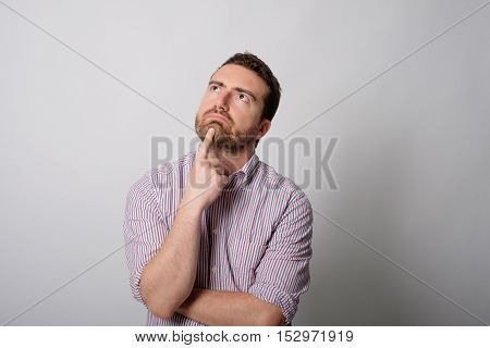 Doubtful man face expresison isolated on gray background