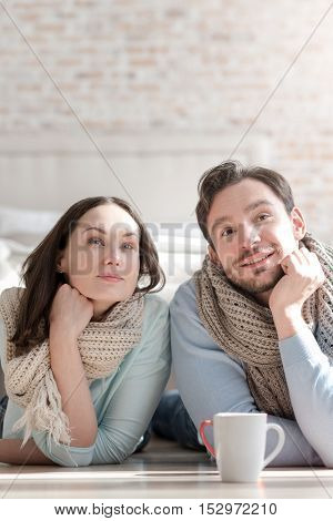 Sweet dreams. Happy positive pleasant couple holding their chins and looking somewhere up while dreaming about something