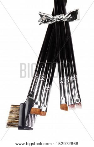Brow makeup brushes set. Metallic bow. Isolated. White background.