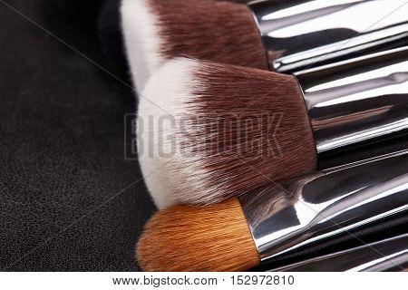 Makeup brushes set on black leather background.