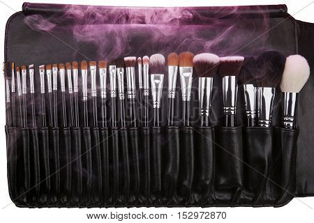 Makeup brushes set in leather case. Pink smoke. Isolated. White background.