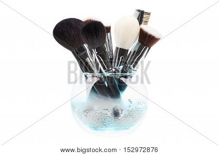 Makeup brushes in glass vase. Crystals. Blue smoke. Isolated. White background.