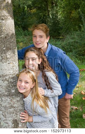 Brother And Sisters Outdoors Smiling At Park