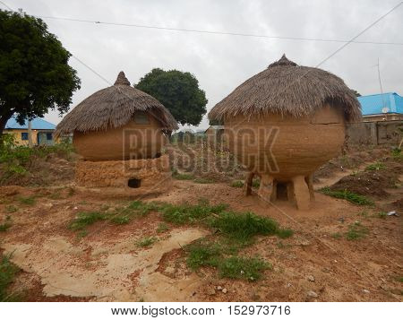 Native silos for rain and food storage in Erena,  Niger State Nigeria. They are usually made from mud with thatched roof. There are small windows to access the inside of the silos. It is usually elevated on stone arrangement. The one on the left has a mud