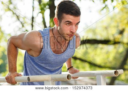 Athletic brunette man pressed on parallel bars at street gym on summer sunny day