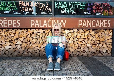 PRAGUE, CZECH REPUBLIC - JUNE 05, 2016: Woman looks at map in the old town square. Tourism in Europe, female tourist with map.