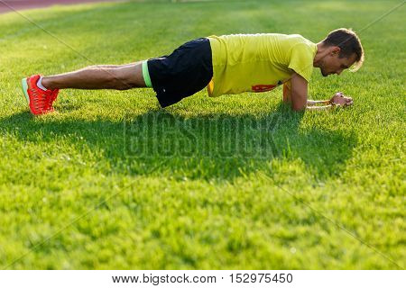 Sporty caucasian man in yellow shirt doing push up on green lawn